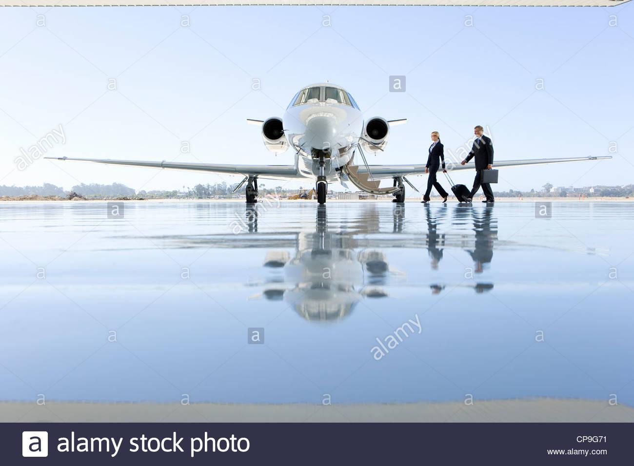 Pilot and flight attendant boarding aeroplane on runway - Stock Image