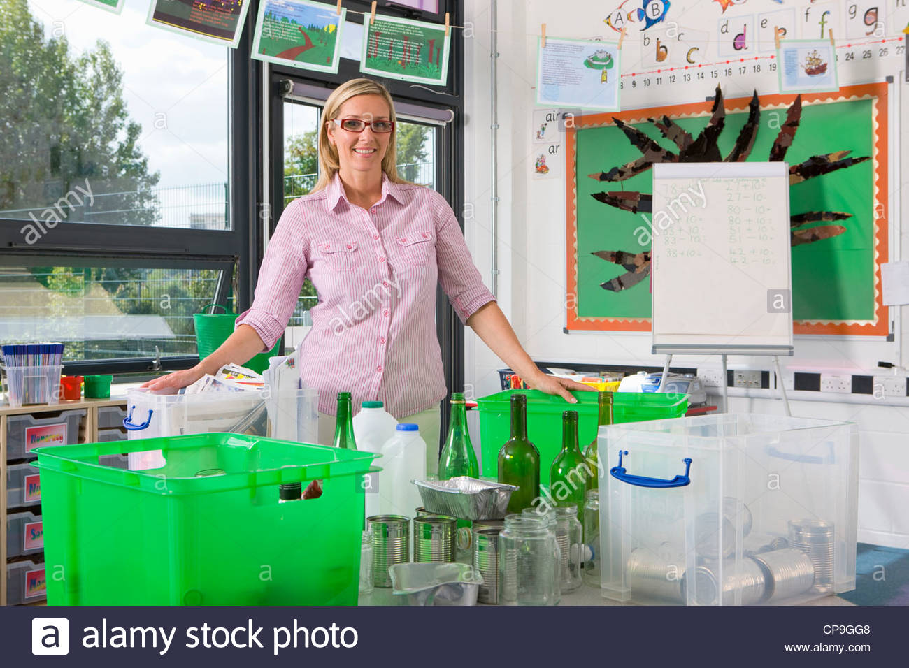 Smiling teacher standing with recyclables and bins in classroom - Stock Image