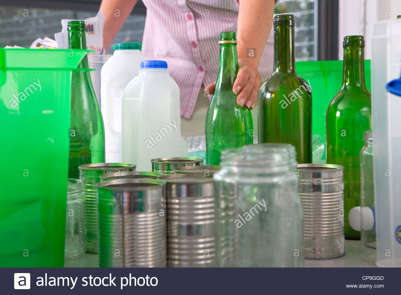 Teacher standing with recyclables and bins in classroom - Stock Image