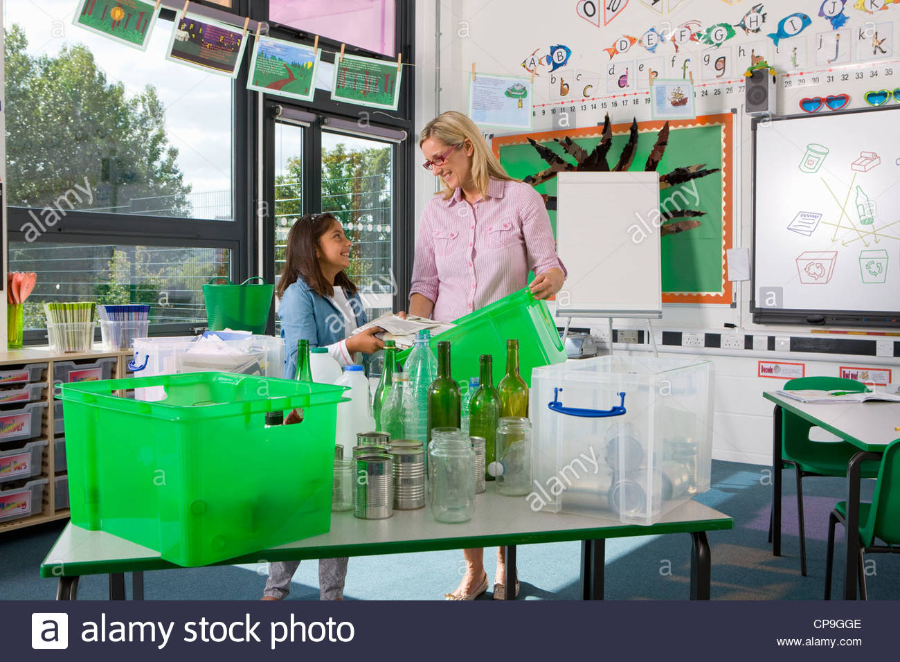 Teacher and student sorting recyclables together in classroom - Stock Image