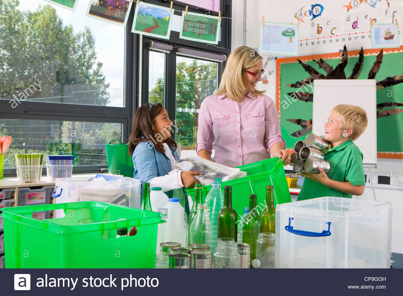 Teacher and students sorting recyclables together in classroom - Stock Image