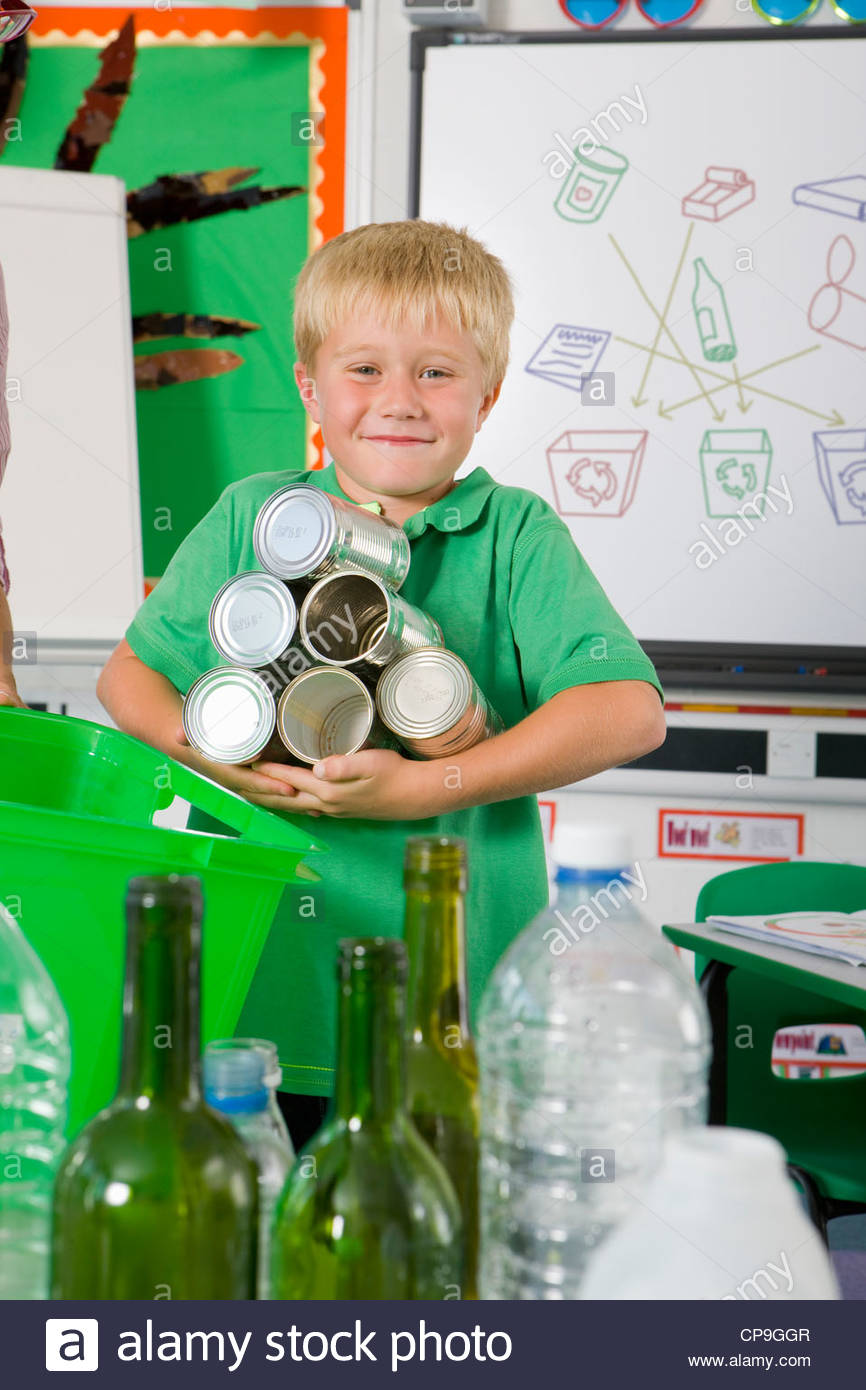 Smiling student holding recyclable tin cans in classroom - Stock Image