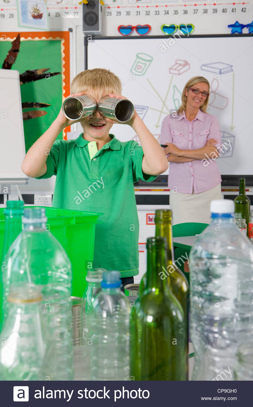 Teacher watching student use recyclable tin cans for binoculars - Stock Image