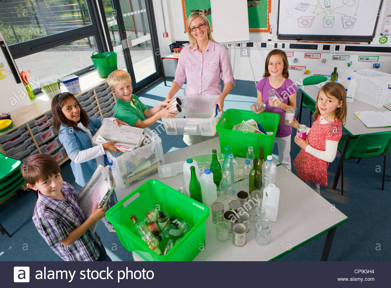 Teacher and students sorting recyclables in classroom - Stock Image