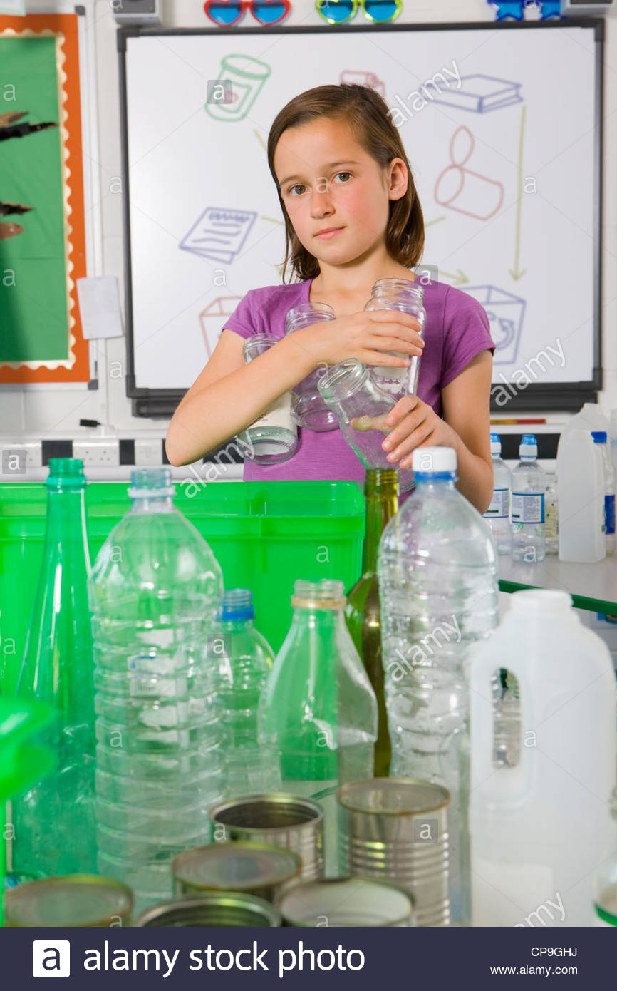Serious student putting glass into recycling bin - Stock Image