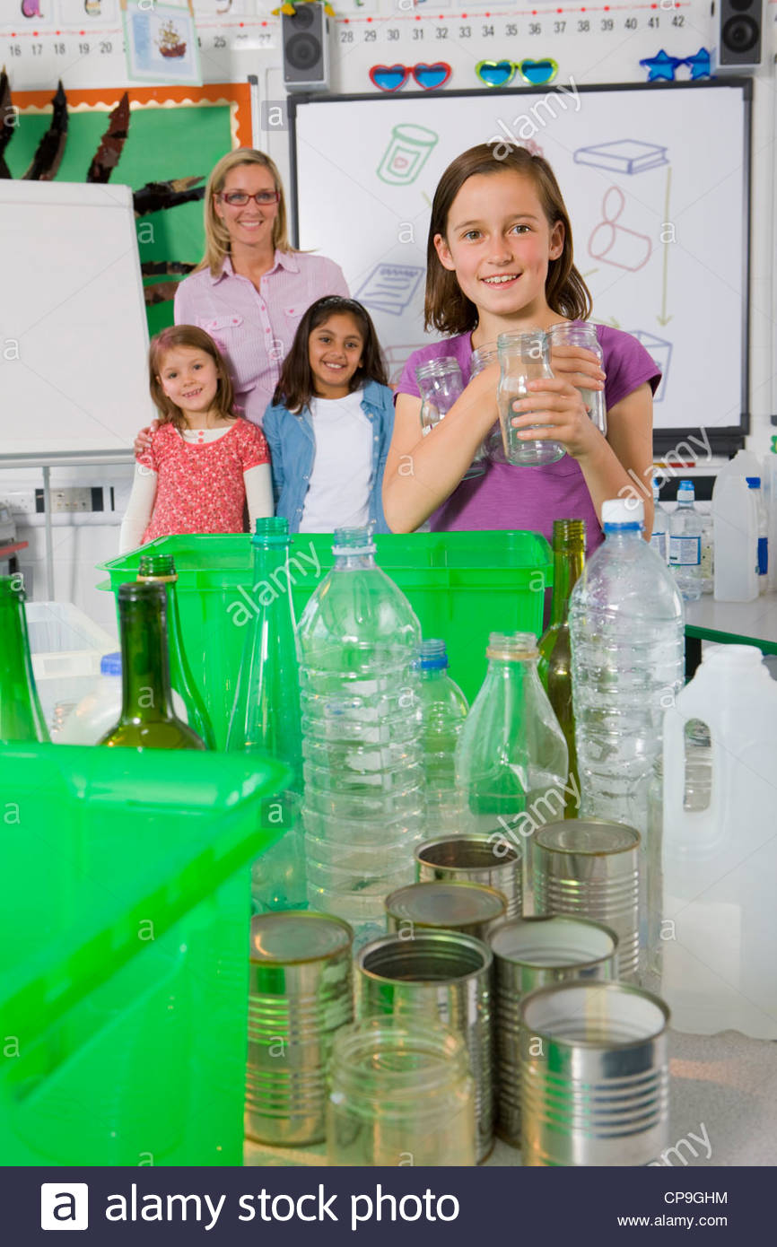 Teacher and students sorting recyclables in classroom together - Stock Image