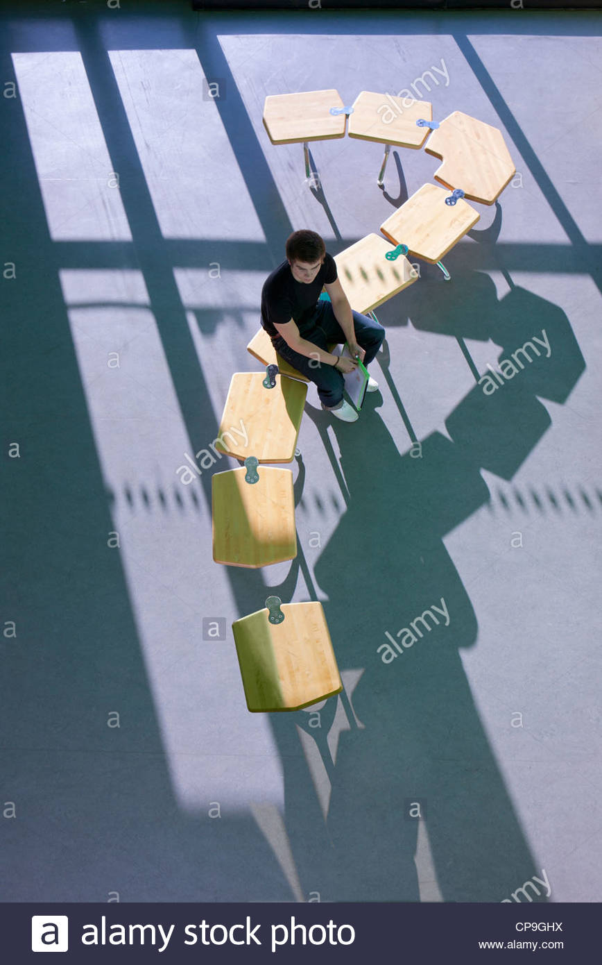 Student sitting on row of school desks formed into a question mark symbol Stock Photo