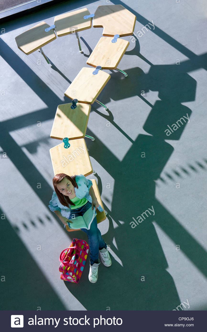 Student sitting on row of school desks formed into a question mark symbol - Stock Image