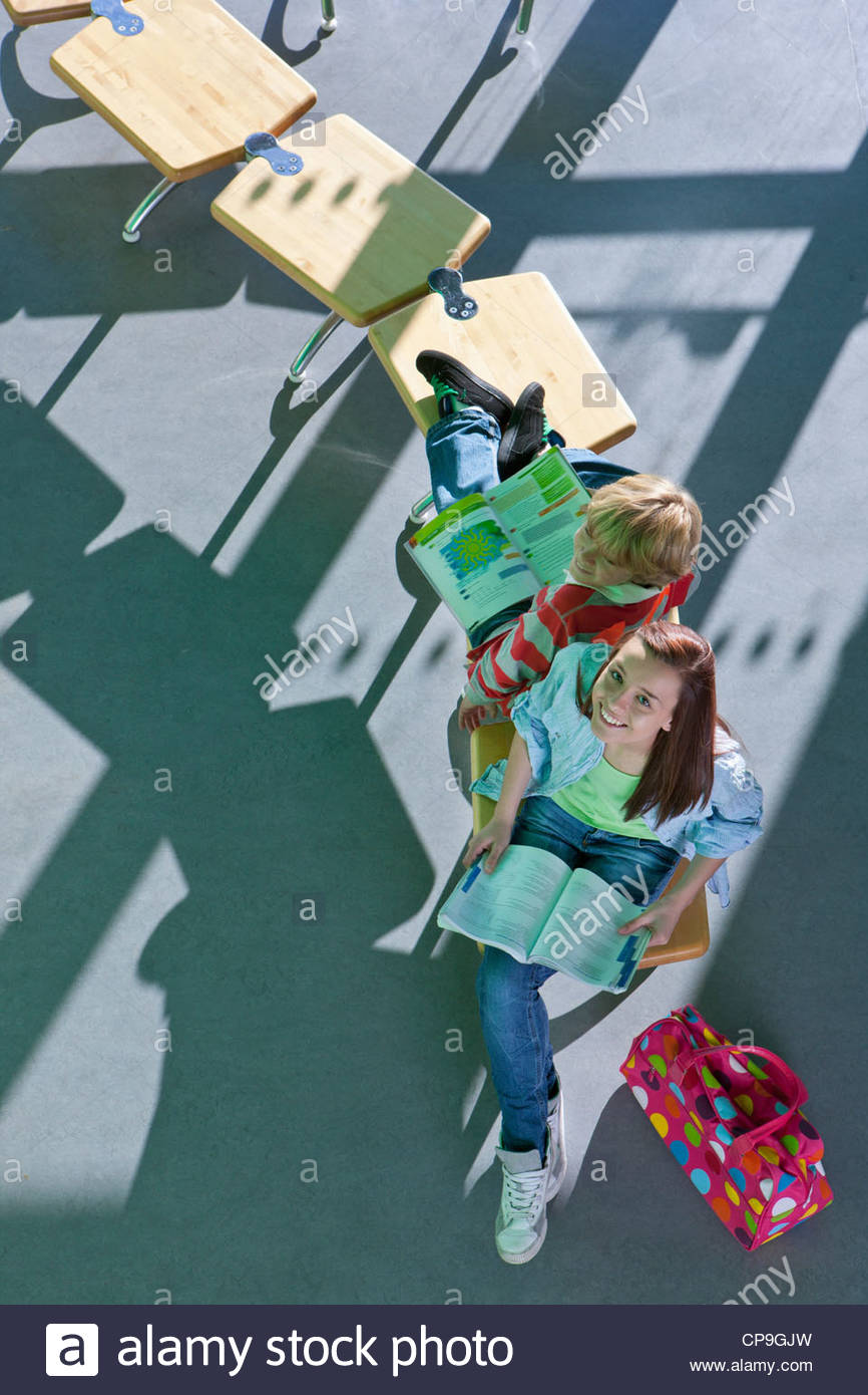 Students sitting on row of school desks formed into a question mark symbol studying - Stock Image