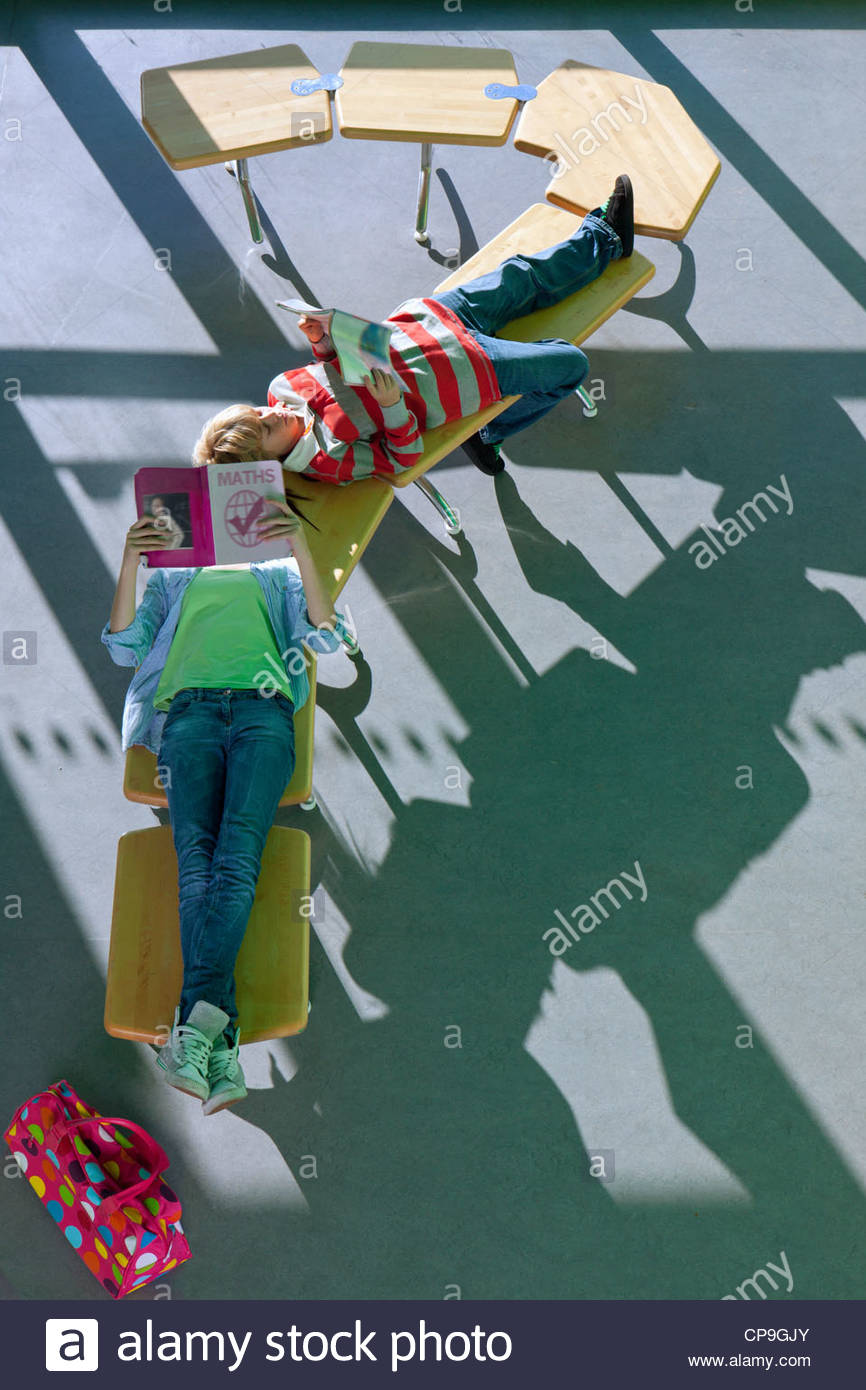Students laying on row of school desks formed into a question mark symbol studying - Stock Image