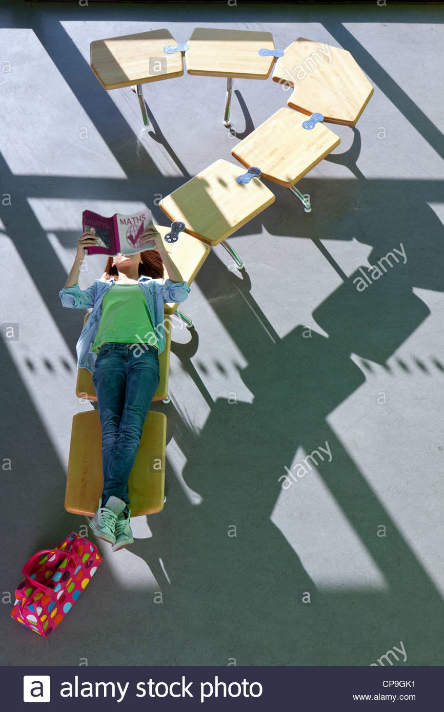 Student laying on row of school desks formed into a question mark symbol studying - Stock Image