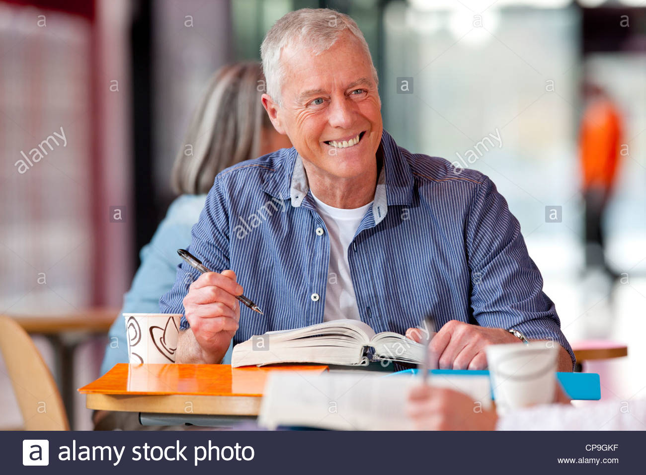 smiling mature student studying textbook - Stock Image