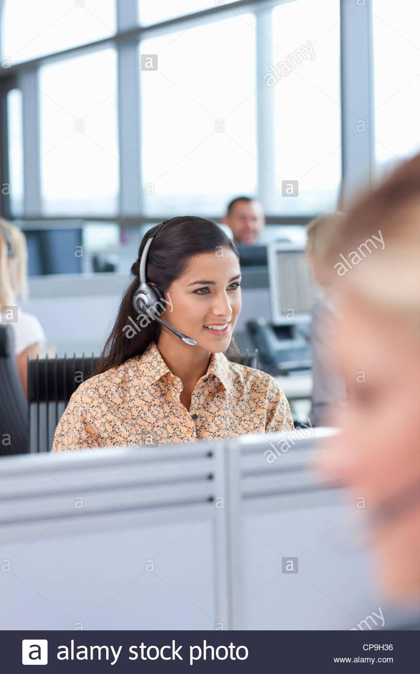Brunette businesswoman wearing headset in office - Stock Image