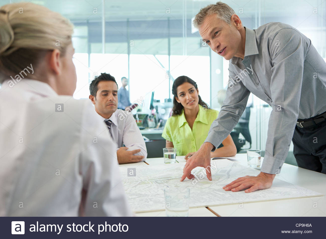 Business people discussing map in conference room - Stock Image