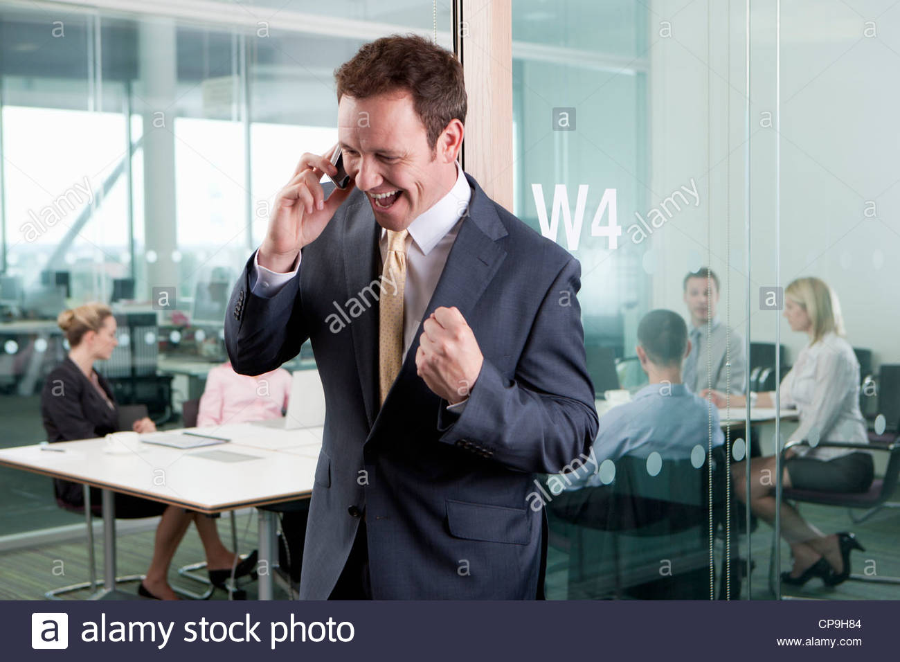 Happy businessman receiving good news on cell phone and gesturing with fist - Stock Image