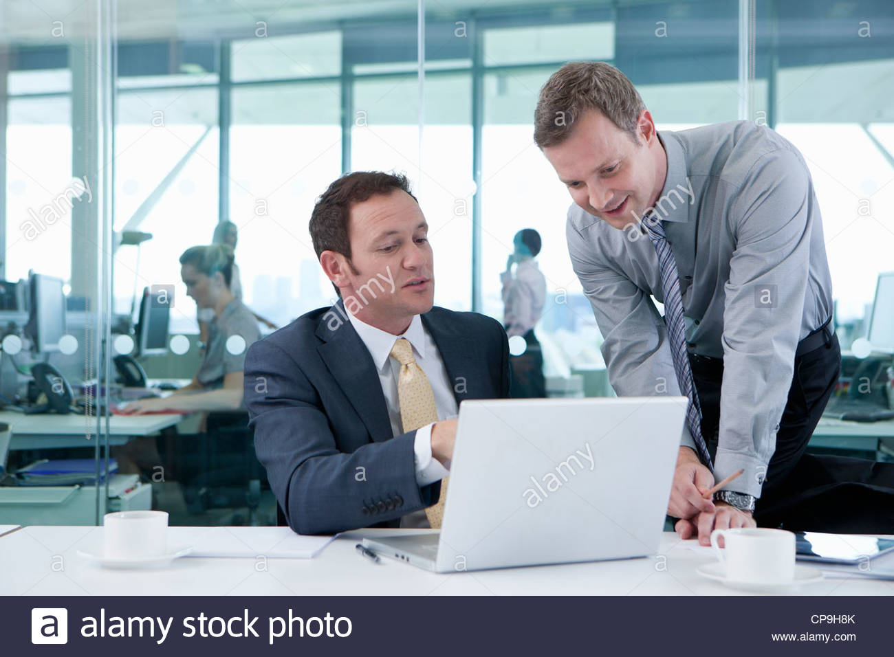 Businessmen working at laptop in conference room - Stock Image