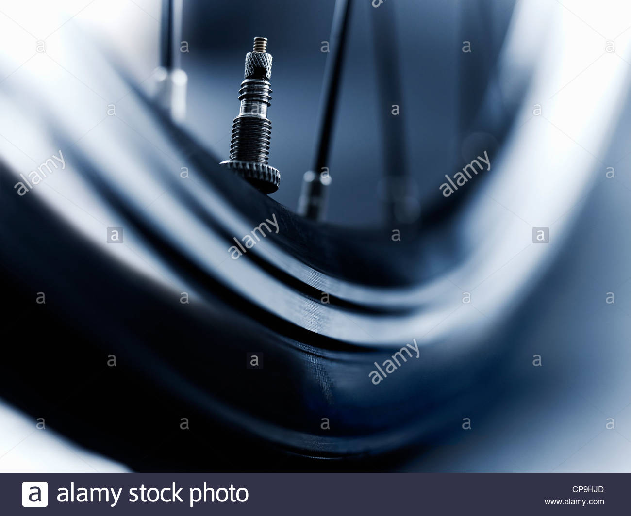 air valve,bicycle,black and white,close up,detail,horizontal,low angle view,metal,no people,photography,studio shot,tire,tire - Stock Image