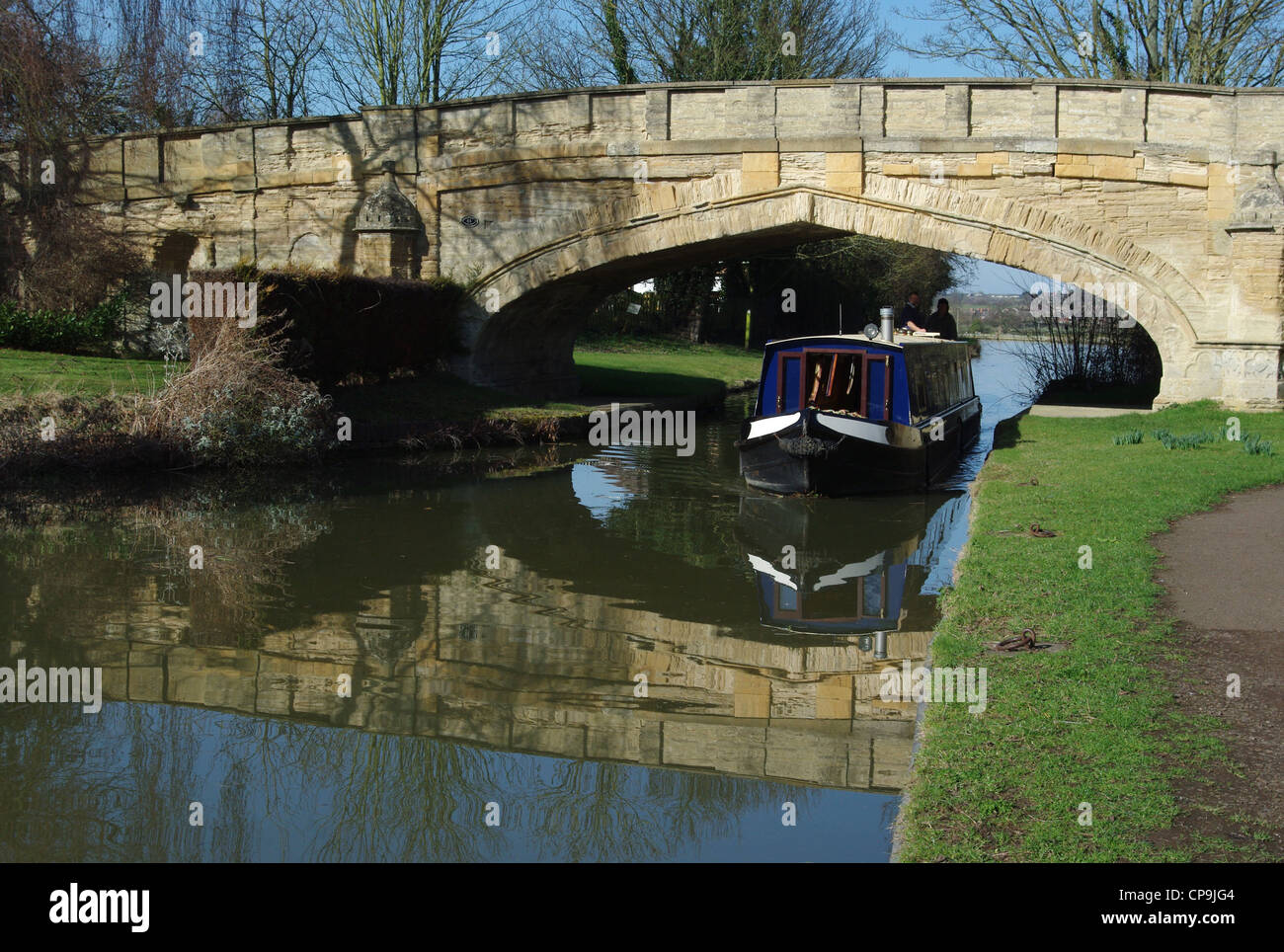 Narrowboat sailing under Solomon's Bridge at Cosgrove. - Stock Image