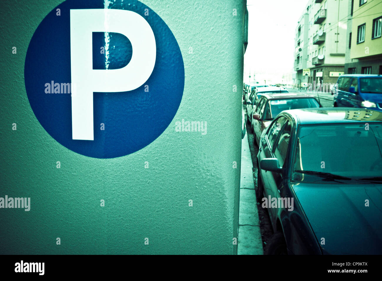 parking sign and cars parked along a street - Stock Image