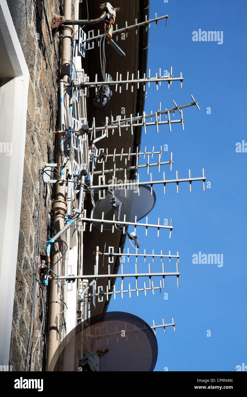 large amount of tv aerials and satellite receivers on a wall of a tenement building in Scotland uk - Stock Image