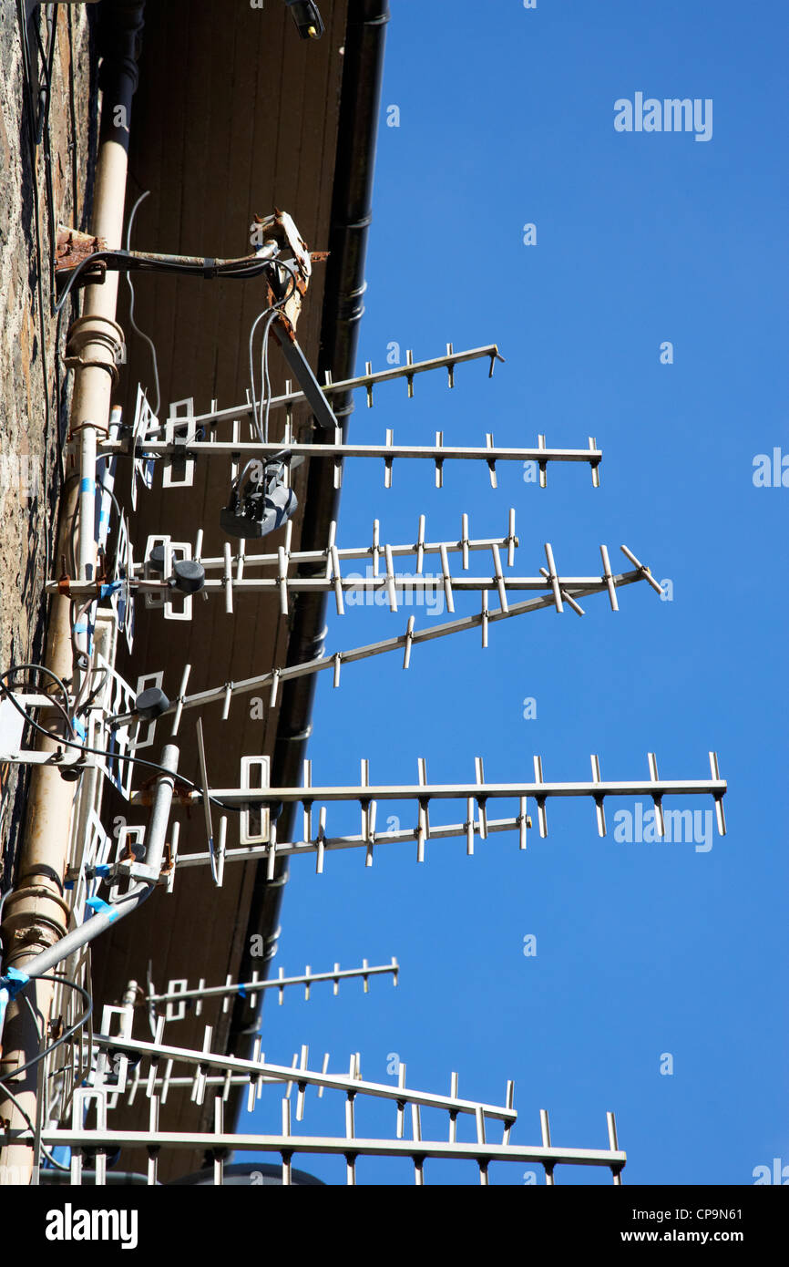 large amount of tv aerials on a wall of a tenement building in Scotland uk - Stock Image