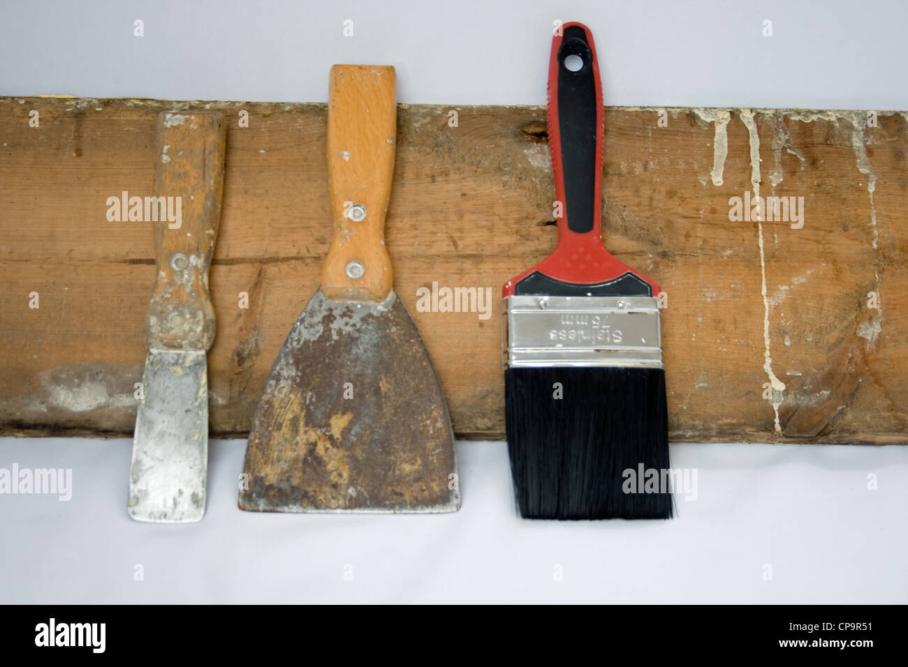 https://c8.alamy.com/comp/CP9R51/painting-and-decorating-tools-leaning-against-a-old-piece-of-skirting-CP9R51.jpg