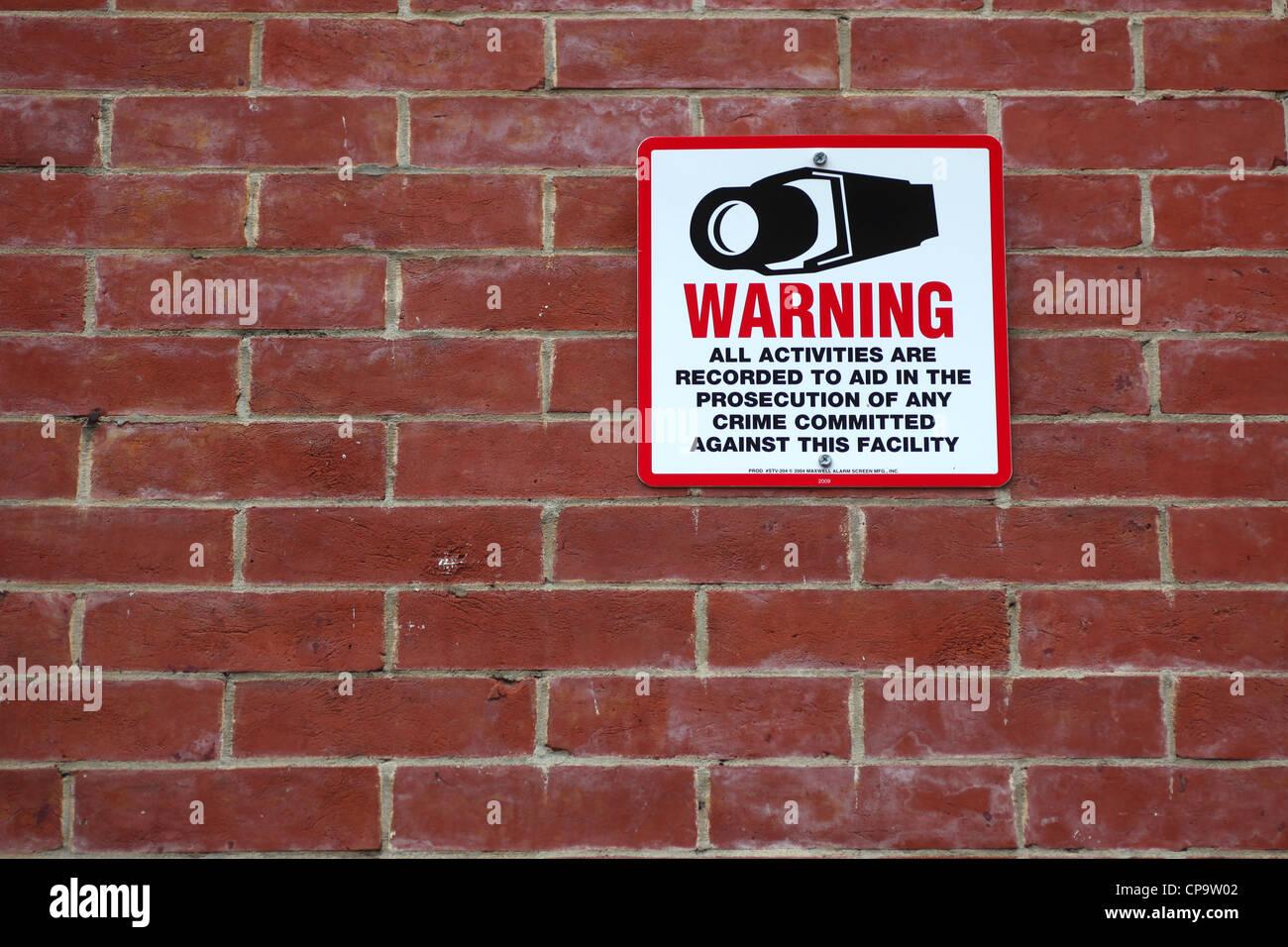 Surveillance warning sign on brick wall - Stock Image