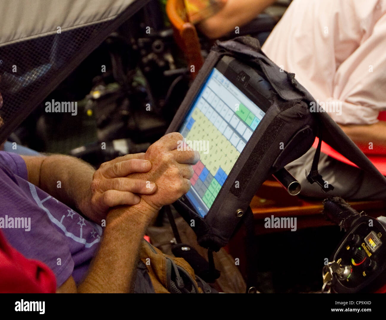 physically disabled man uses touch-screen computer attached to his wheelchair to communicate - Stock Image