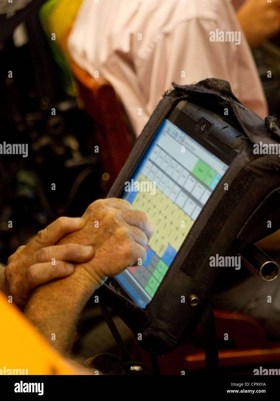 Physically disabled man uses special computer keyboard on his wheelchair to communicate - Stock Image