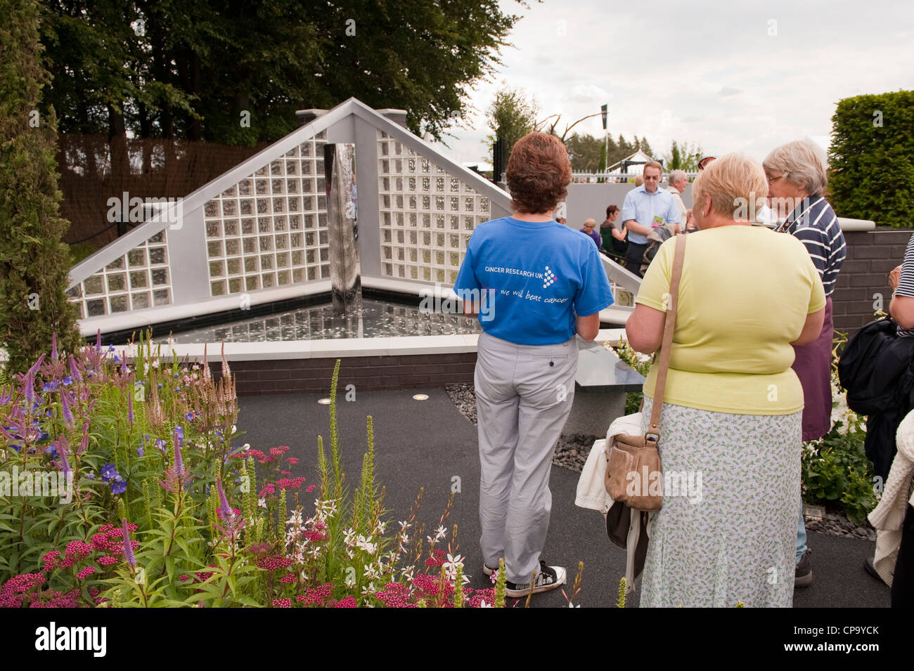 People standing with volunteer worker, viewing water feature in SHINE Garden for Cancer Research UK - RHS Flower - Stock Image