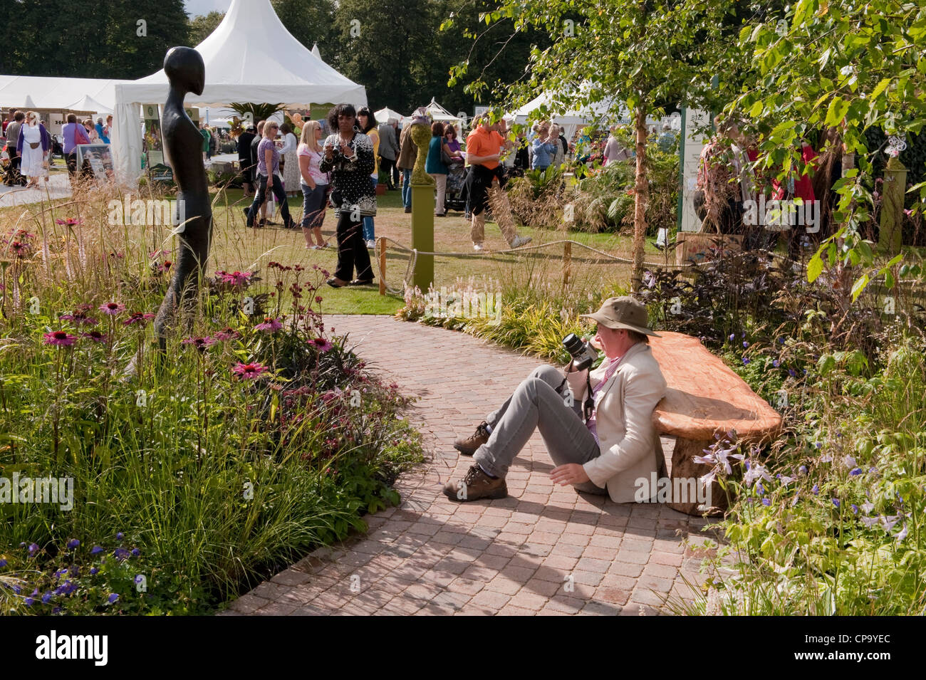 Designer Sue Beesley taking photo of sculpture in her 'Grasses with Grace' show garden - busy RHS Flower - Stock Image