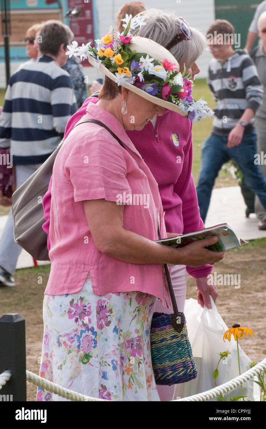 Close-up of lady wearing straw hat decorated with colourful summer flowers, standing & reading guide book - - Stock Image