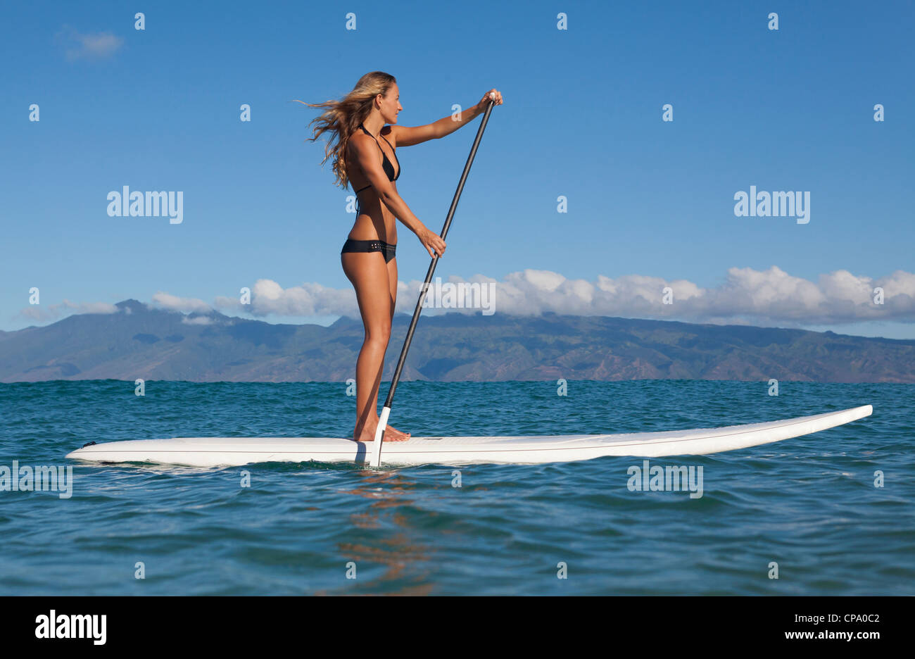Fit, athletic woman stand up paddles at Napili Bay, Maui, Hawaii with Molokai in the distance. - Stock Image