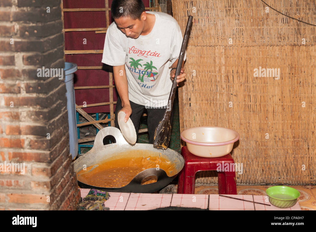 Vietnamese man beside a simmering pan of coconut candy ingredients, Cuu Long, Cai Be, Mekong Delta, Vietnam - Stock Image