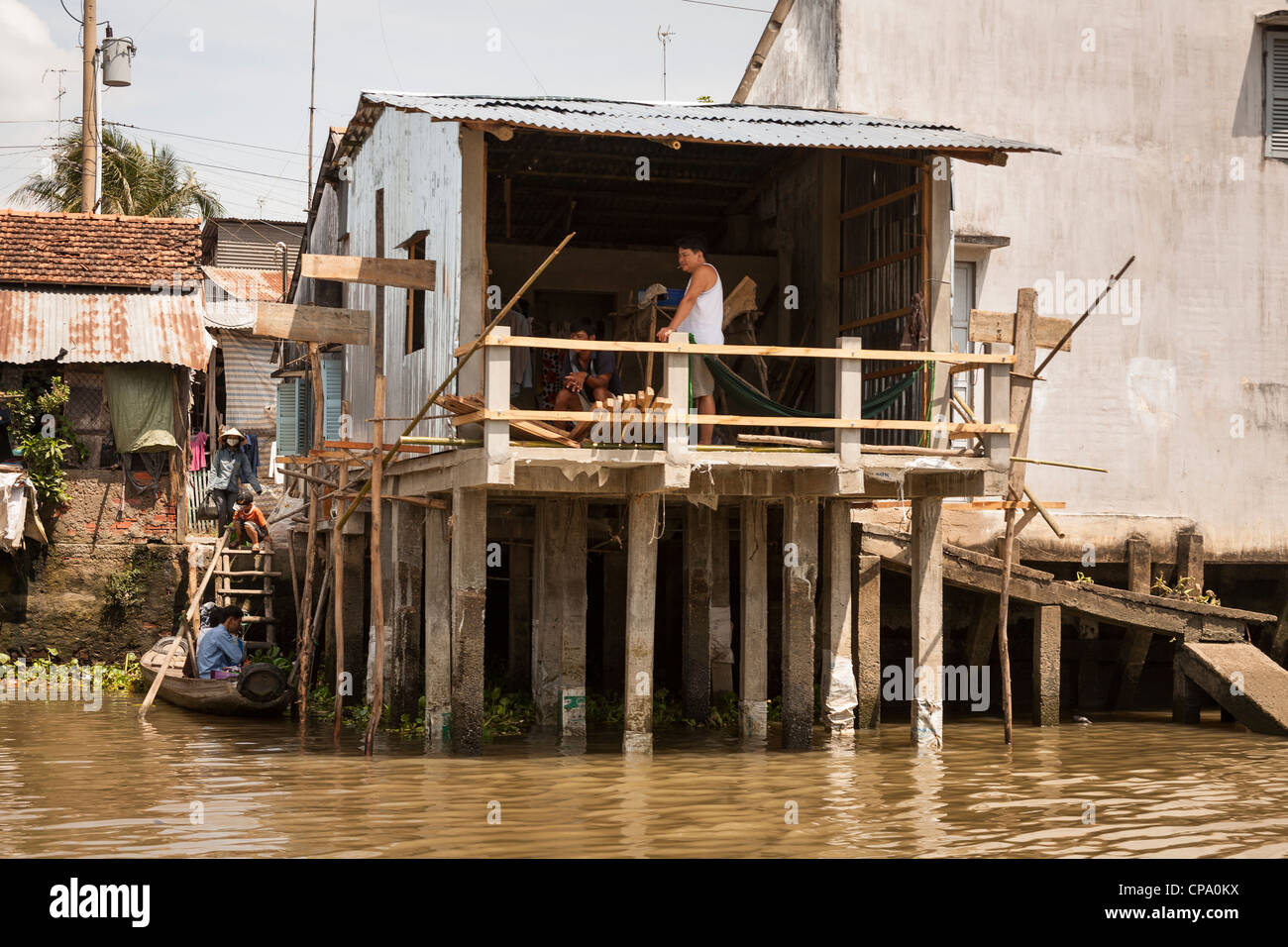 Riverside house supported by stilts, Cai Be, Mekong River Delta, Vietnam Stock Photo