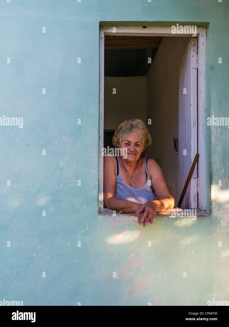 A 60-70 year old Cuban woman looks out of her window and leans her arms on the window sill in Viñales, Cuba. Stock Photo