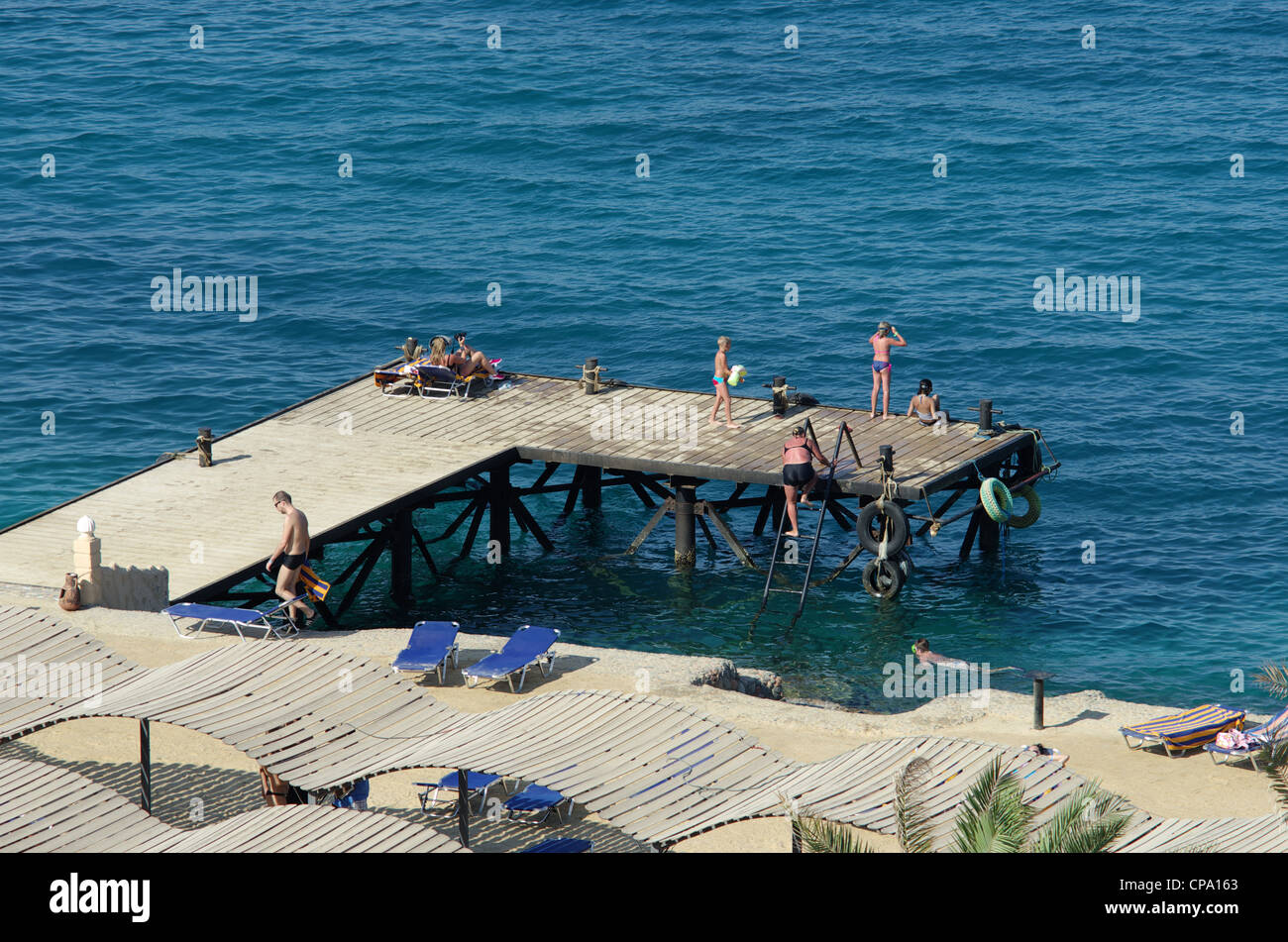 People on a tropical beach, pier, berth, coast of Red Sea, hotel resort Sphinx, Hurghada, Egypt, Africa - Stock Image