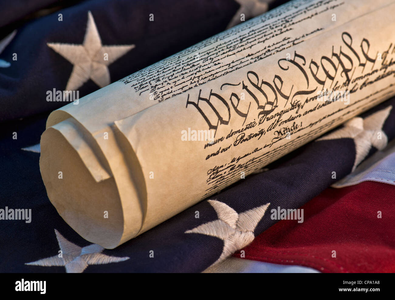 We The People - U.S. Constitution atop an American flag background. - Stock Image