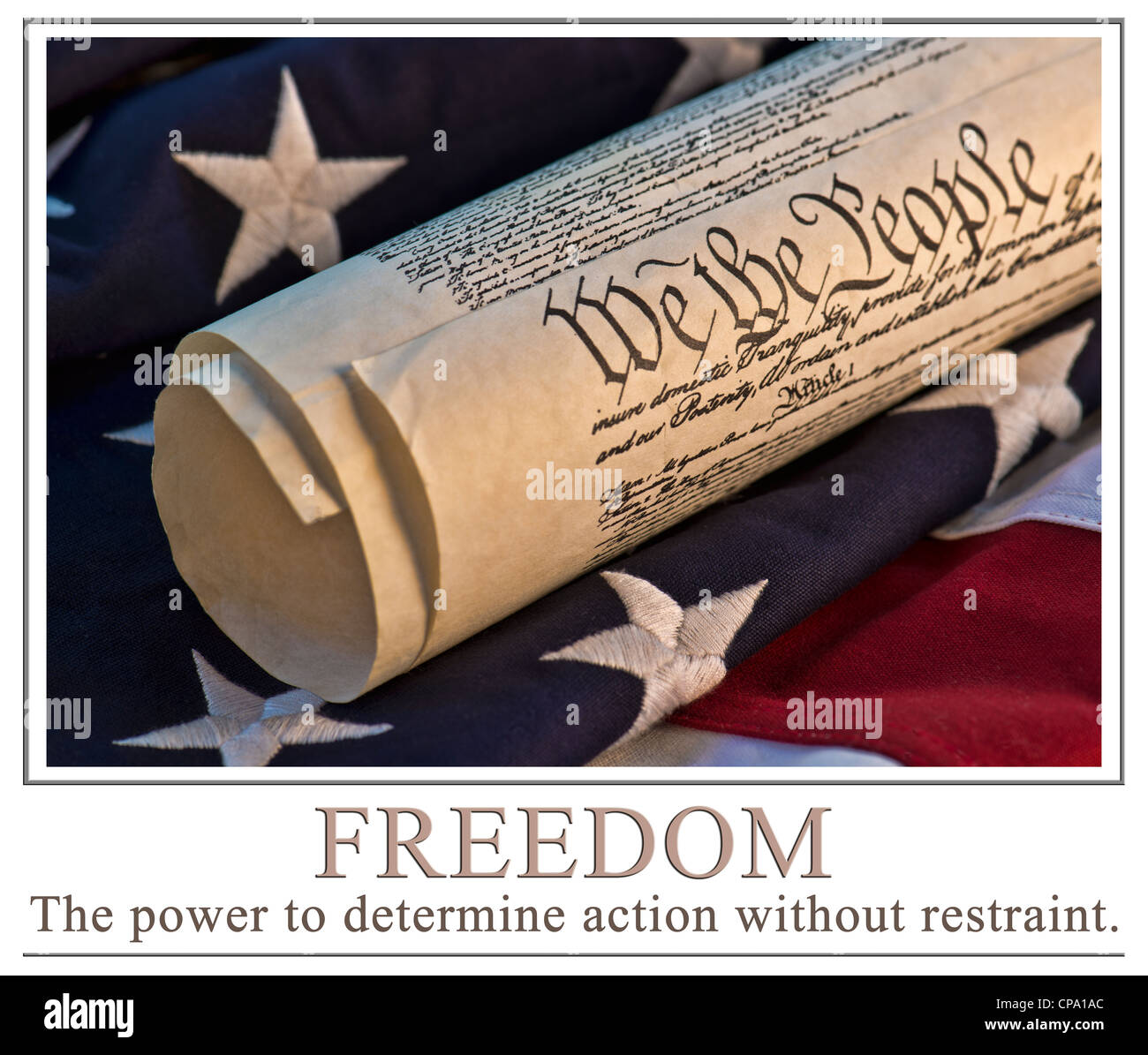 U.S. Constitution atop an American flag background. The words 'Freedom - the power to determine action without - Stock Image