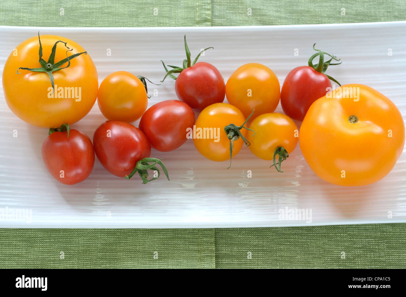 Red and yellow cherry and medium size tomatoes on white oblong dish - Stock Image