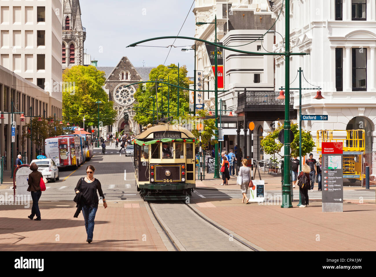 A busy street scene in central Christchurch with a tram, tourists, coaches and the cathedral in the background. - Stock Image