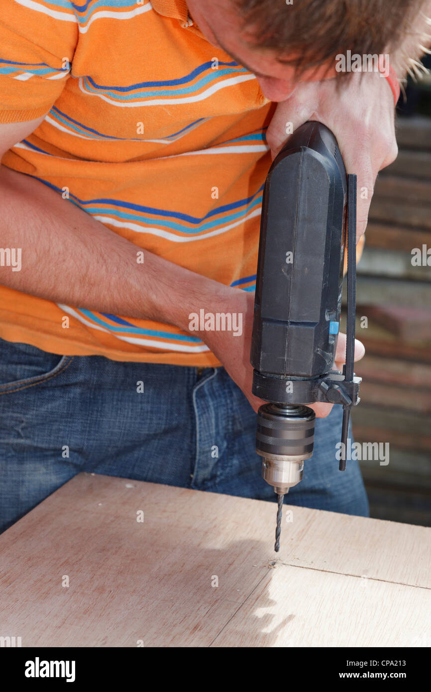 Man drilling into wood with an electric power drill powertool - Stock Image