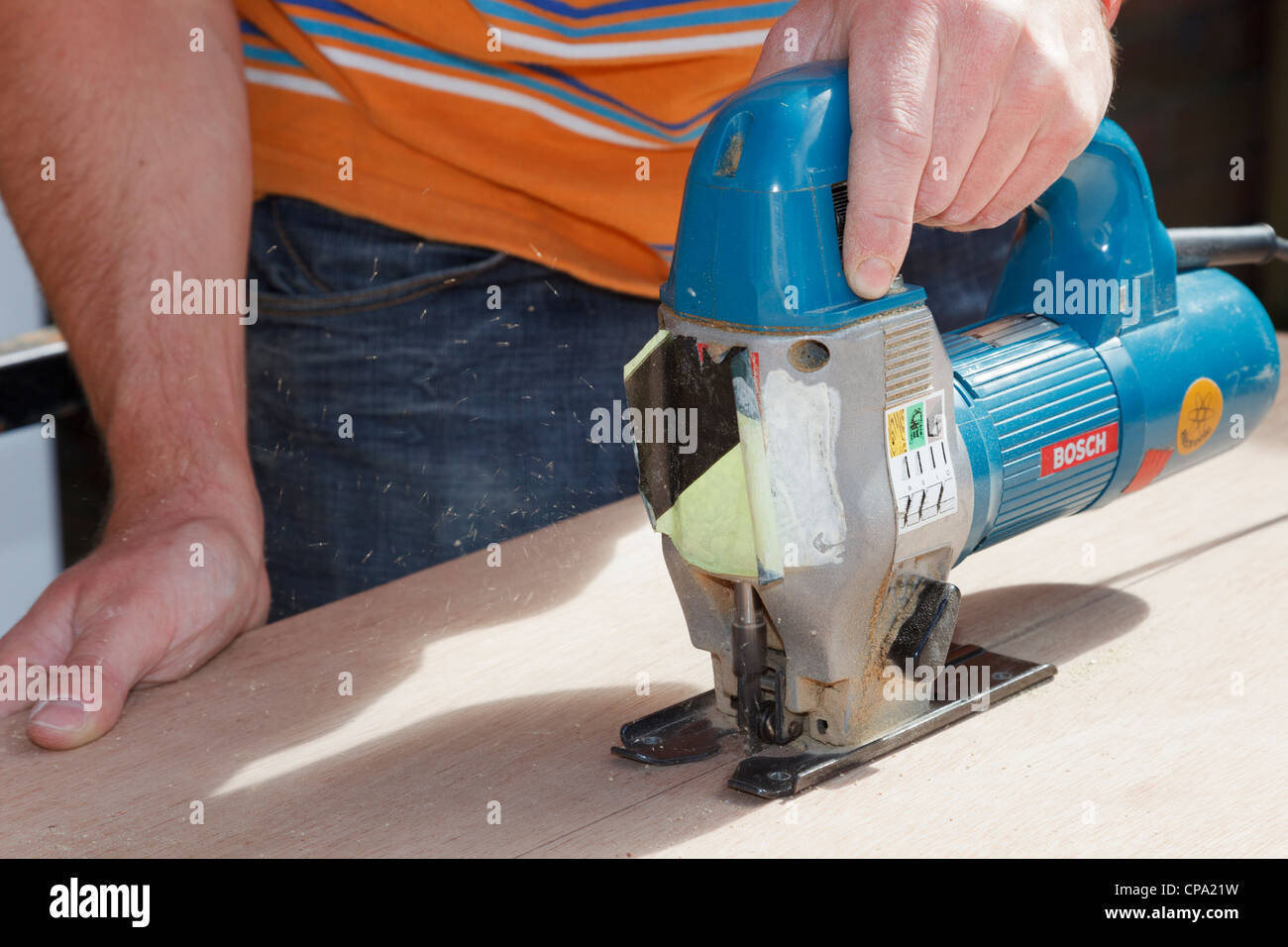 A young man carpenter cutting wood with an electric Bosch jigsaw powertool. England UK Britain - Stock Image