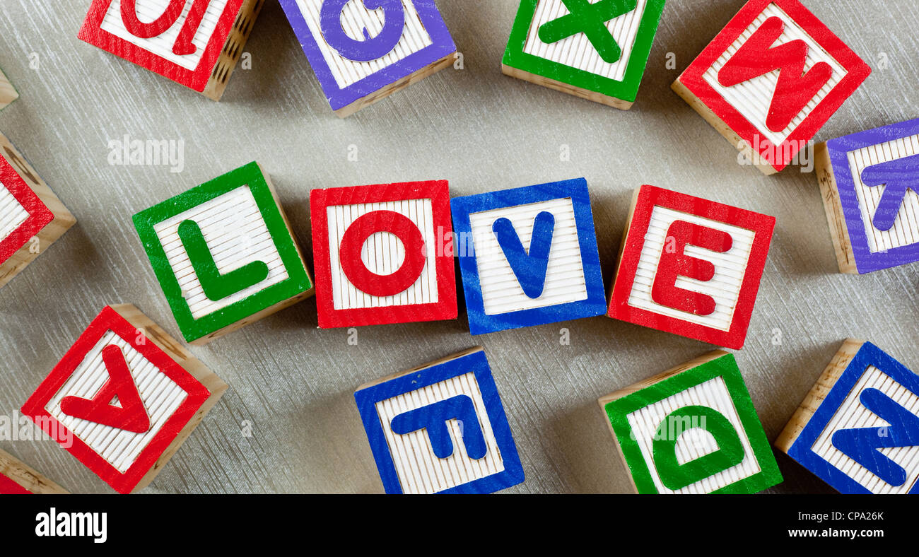 Wooden blocks forming the word LOVE in the center - Stock Image