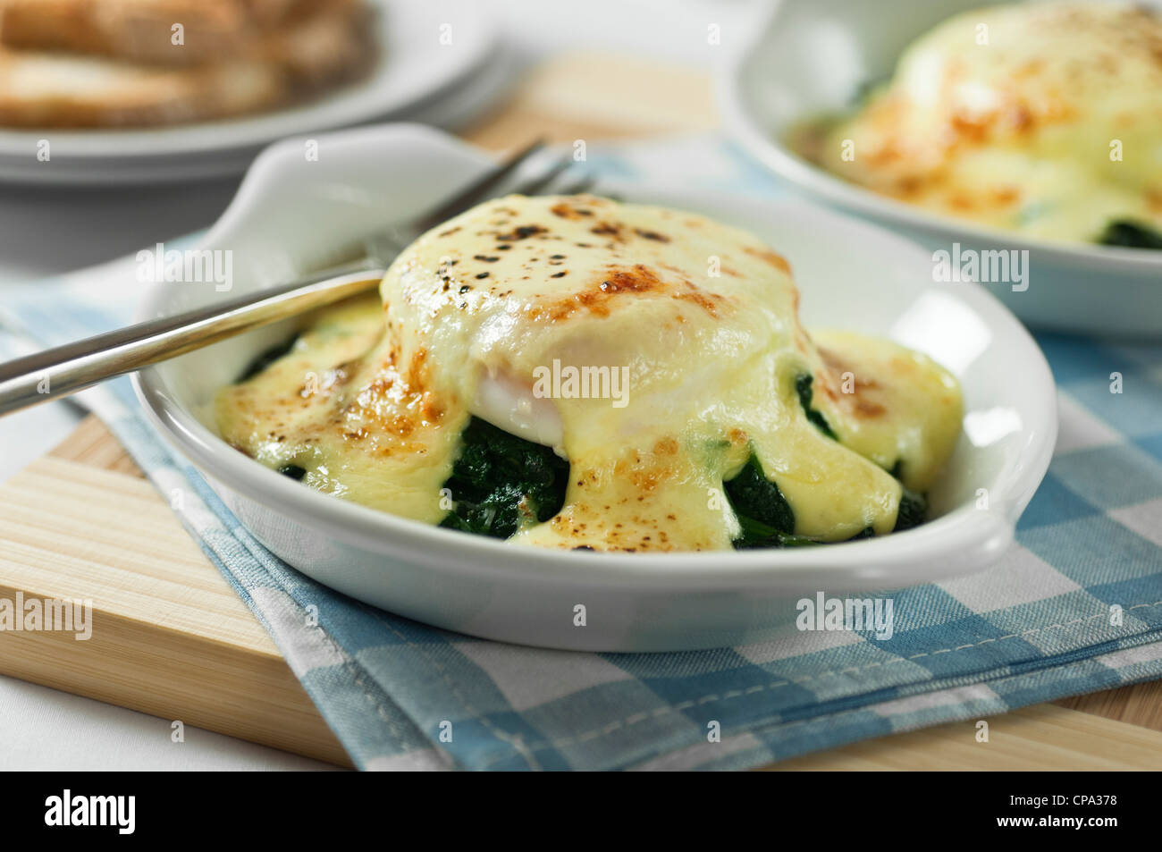 Eggs florentine. Poached eggs on spinach with cheese sauce. - Stock Image