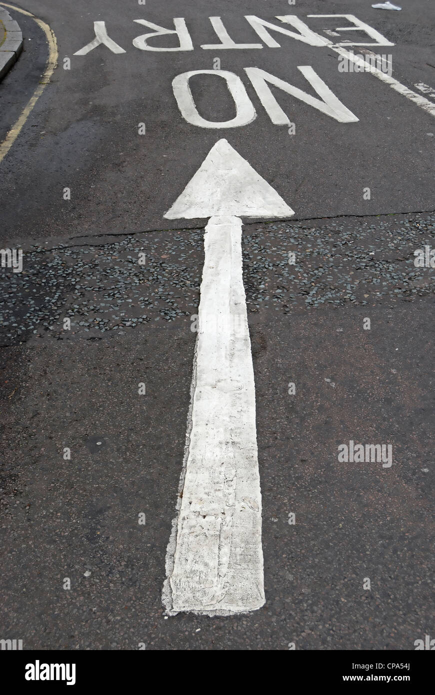 road markings with arrow pointing towards no entry instruction for traffic approaching in opposite direction - Stock Image