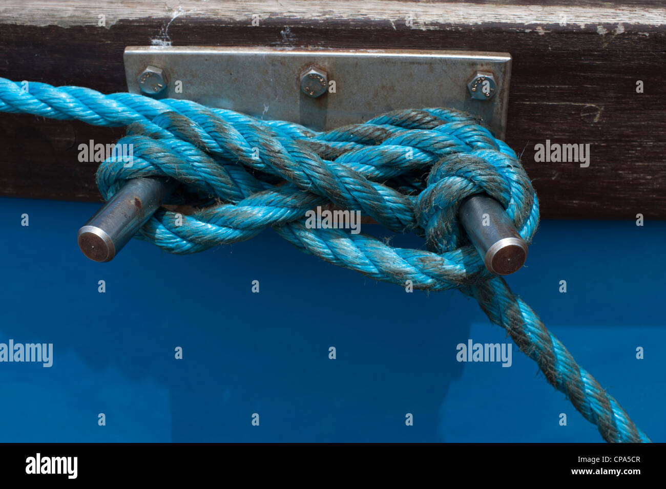 Blue nylon rope tied round metal on a fishing boat - Stock Image