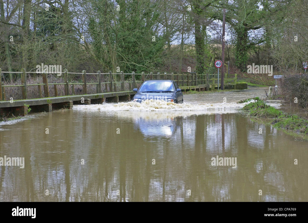 Vehicles passing through floods in Sussex - Stock Image