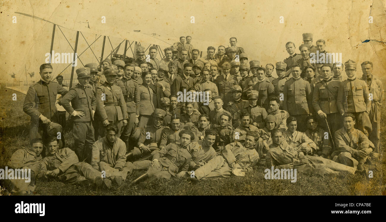 World War I-era photograph of Italian army soldiers in front of an old biplane. - Stock Image