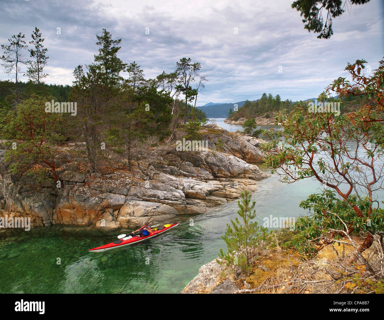 a sea kayaker paddling through The Curme Islands in Desolation Sound, British Columbia - Stock Image